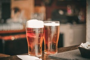 photo of two pilsner glasses on a bar